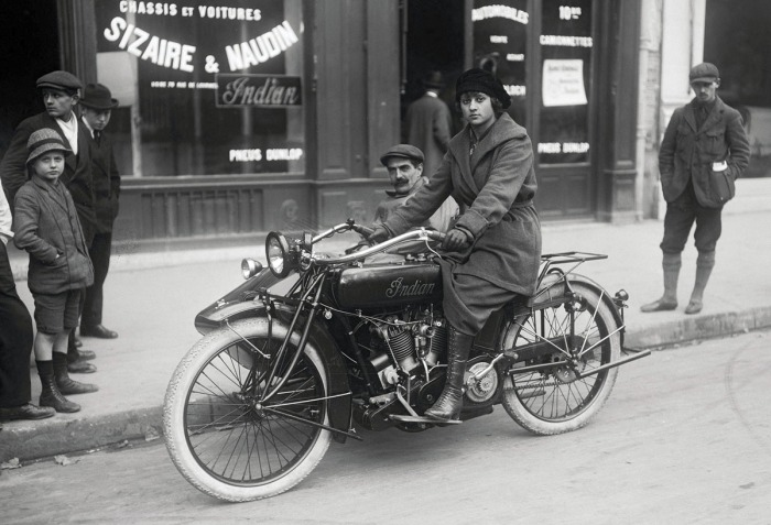Woman on an 'Indian' motorcycle coupled with a sidecar in Paris